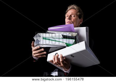 Overworked Mature Businessman Holding Pile Of Folders And Looking At Camera Isolated On Black