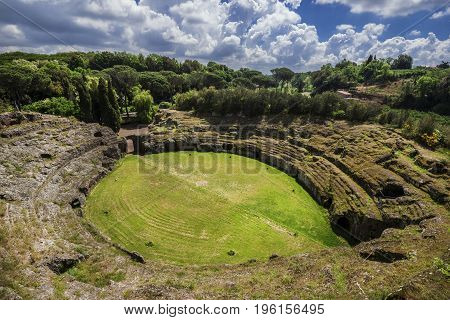 Ancient roman tuff stone amphitheater in the town of Sutri with clouds near Rome