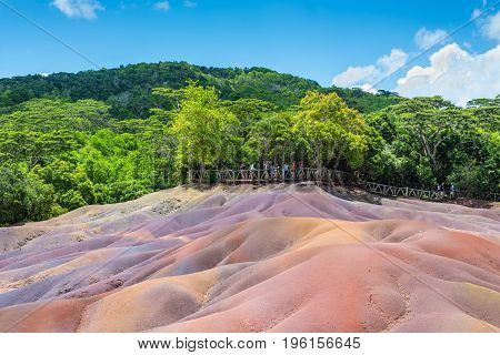 Chamarel Mauritius - December 26 2015: People watching for main sight of Mauritius - Seven Coloured Earth in Mauritius Chamarel nature reserve. Green forest behind and blue cloudy sky.