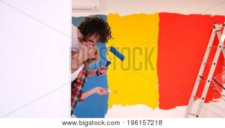 portrait of happy smiling young couple painting interior wall of new house  peeking from behind the wall