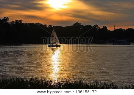 A canoe boat sails along the evening river.