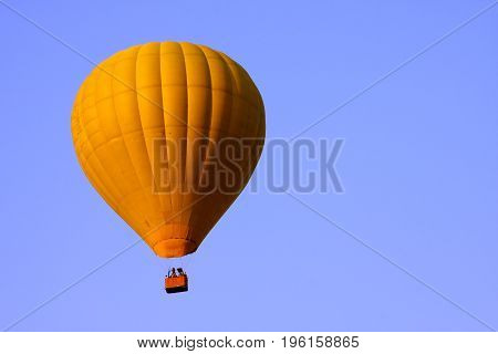 Yellow hot air balloon on blue sky background.
