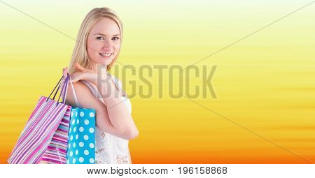 Digital composite of Shopper with bags against blurry yellow background