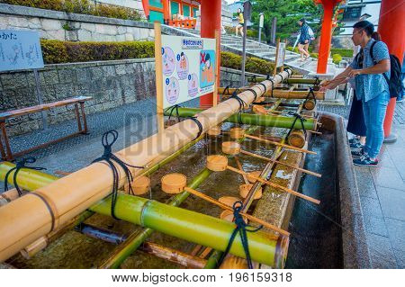 KYOTO JAPAN - NOVEMBER 24, 2016: Unidentified people washing their hands at hand wash pavilion in Fushimi Inari Shrine in Kyoto, Japan.