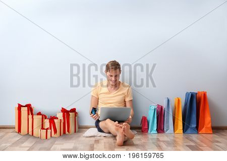 Internet shopping concept. Man sitting with laptop and purchases near wall at home