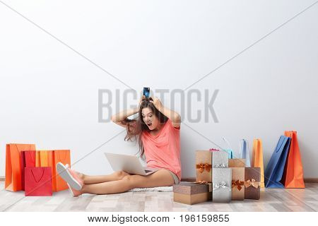 Internet shopping concept. Woman sitting with laptop and purchases near wall at home