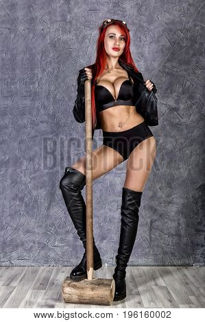 sexy steampunk woman in underwear and sunglasses holding cricket hammer over grey background