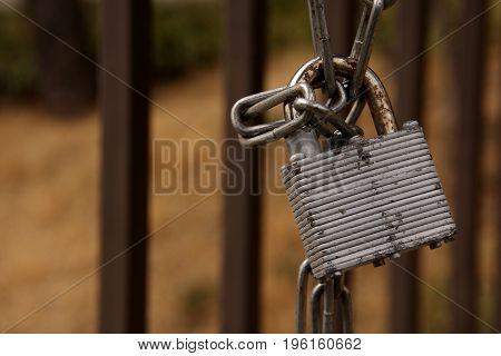 Grungy padlock lock with chain on garden door.