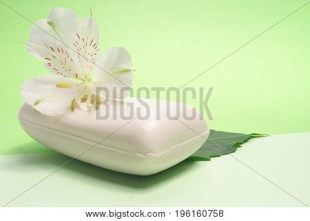 Soap and flower Alstromeria on a green background. Spa