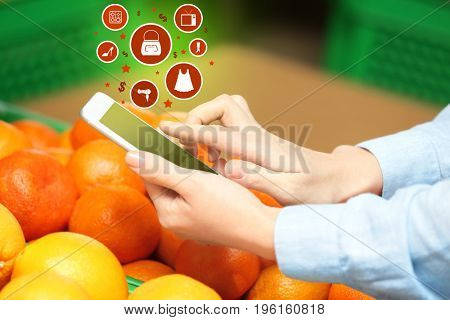 Woman using smartphone for browsing internet store, closeup. Online shopping concept