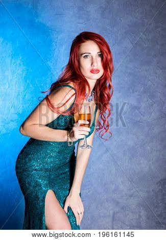elegant sexy woman with big boobs in tight blue dress holding wineglass with champagne.