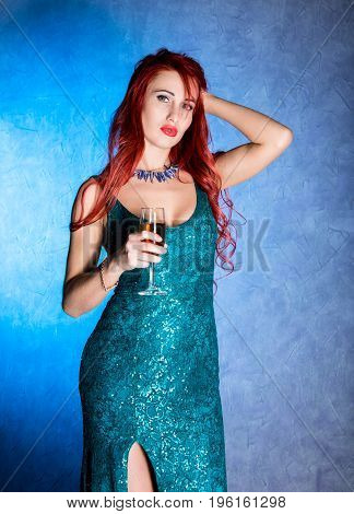 elegant redhead woman with big boobs in tight blue dress holding wineglass with champagne