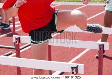 High school girls doing hurdle drills working on her trail leg at track and field practice