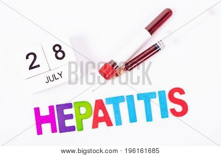 28 July calendar wood and sample blood with hepatitis wooden letters word. World hepatitis day concept.