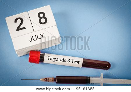 28 July calendar wood and sample blood for hepatitis B test. World hepatitis day concept.