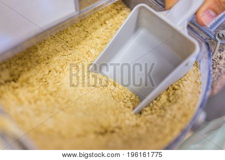 Person Scooping Nutritional Yeast From Bulk Section