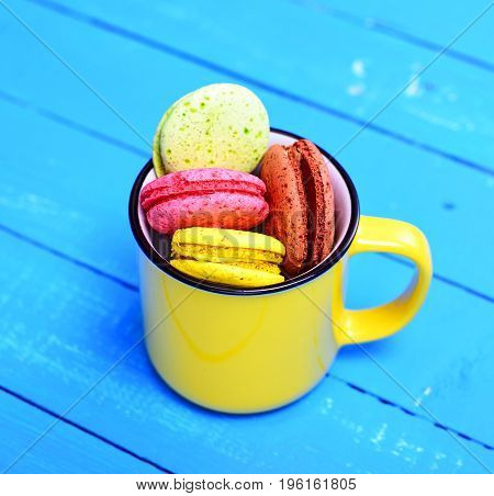 French cake made from egg white and almond flour macarons in a yellow ceramic cup on a blue wooden background top view
