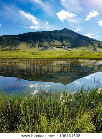 A mountain peak with green hills is reflected in a lake