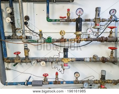 Many copper pipes with gauges and dials for plumbing a building