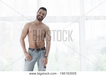 Sexy fashion portrait of a hot bearded male model in stylish jeans with muscular body posing in modern interior setting with window light