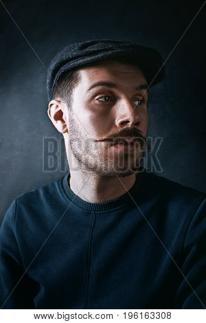 The young man in cap looking away on black background