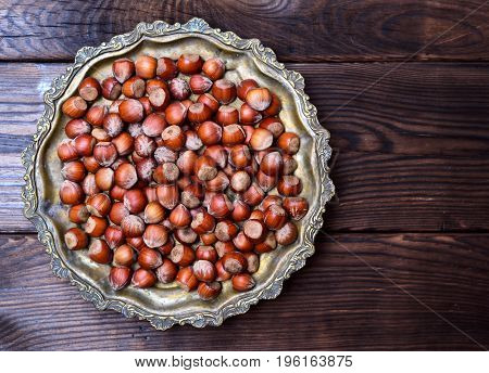 Hazelnut nut in shell on an iron copper plate view from above