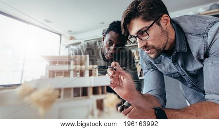 Two male architects in office discussing over house model. Architect working on an architectural model.