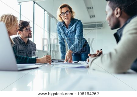 Businesswoman standing and leading business presentation. Female executive putting her ideas during presentation in conference room.
