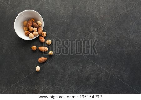 Assortment of nuts in a bowl on dark background with free space for text. Healthy snack for beer.