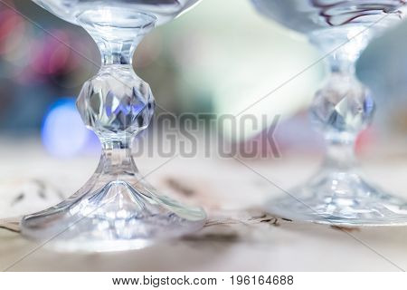 Macro Closeup Of Two Crystal Wine Glasses Legs With Blue Bokeh Lights