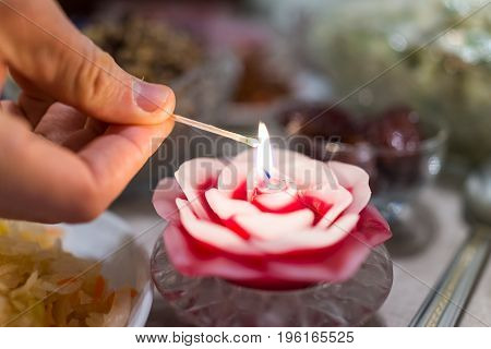 Hand Lighting Rose Flower Candle With Match Stick In Glass Bowl On Table