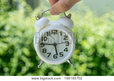 Closed up of woman hand holding white alarm clock as business or time countdown concept with green bokeh background.
