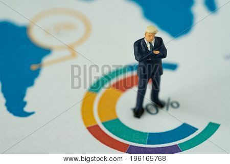 Miniature people business concept as small figure businessmen standing on analysis graph chart.