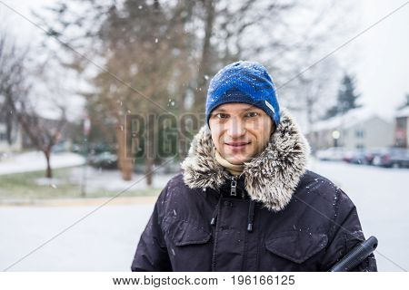 Portrait of man in winter coat and blue hat during winter snow
