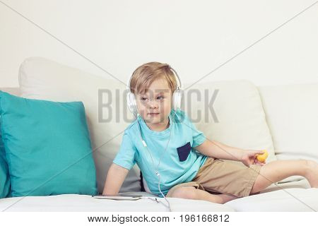 3 Year Old Boy Sits On The Couch And Listens To Music. Little Cute Boy Watching Cartoons On The Phon