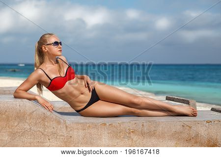 Beautiful blonde woman in the red bikini and sunglasses sitting on the lonely evening beach with turquoise water and white sand in the rays of the setting sun. Zanzibar. Nungwi.