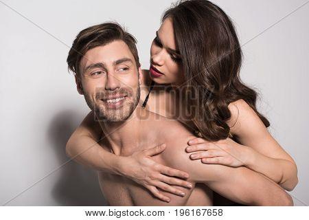 Portrait Of Beautiful Sensual Couple, Man Giving Woman Piggyback Ride On Grey