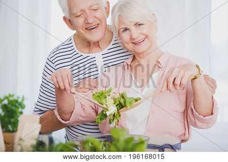 Elder Woman And Man Preparing Salad