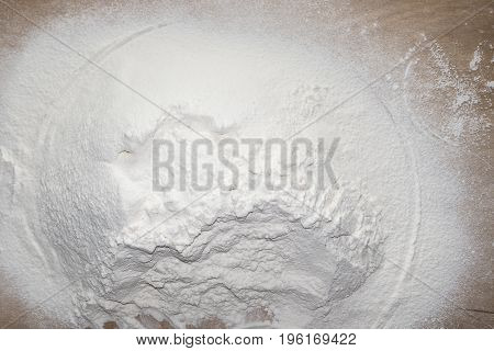 White flour on wooden table. Food background.