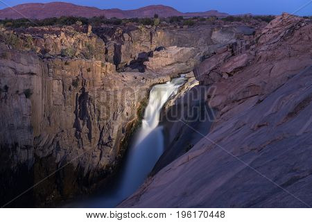 The main Augrabies waterfall after sunset lighted by a single electric light