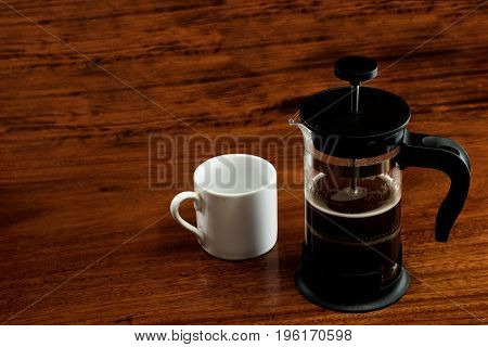 White cup and french press coffee or jug