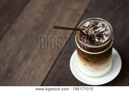 Iced coffee with milk on  wooden table