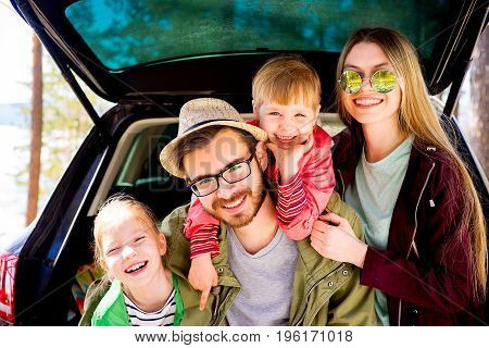 Happy family of four going on a car trip