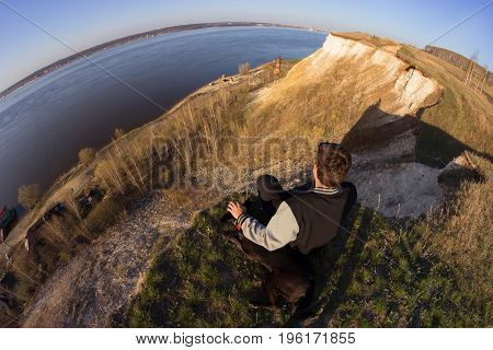 man and dog sitting on agde of the hill view from above. fisheye lens