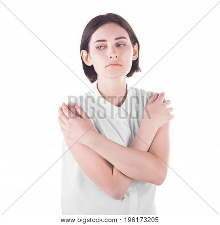 A cute and young girl in a white blouse holds her hands on her shoulders and looks thoughtful, isolated on a white background. A beautiful young woman in elegant blouse and with short dark brown hair.