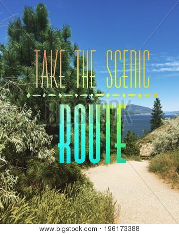Motivational text in colorful font on scenic lake and mountains landscape from hilltop with hiking trails. Take the scenic route.