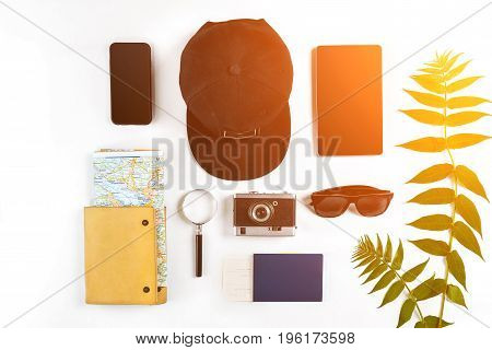 Travel accessories set on white background: smart, passport, cap, notepad, map, camera and sunglasses. Top view point. Flat lay. Still life. Sun flare