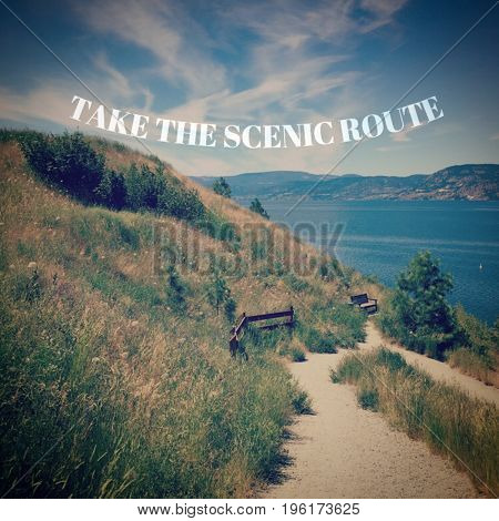 Motivational text in white font on scenic lake and mountains landscape from hilltop with grass. Trails on hillside and along shoreline with parasol on beach.
