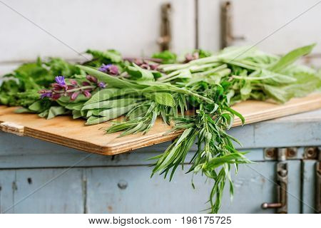 Assortment of fresh herbs mint, oregano, thym, blooming sage on cutting board over old blue white wooden kitchen table. Rustic style, day light.