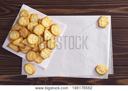 Crackers biscuits with cheese flavor on wooden table and empty paper for text top view